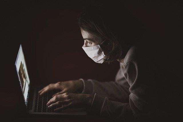 Persoană cu mască scriind la laptop